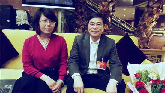 赖坤洪(右)与记者合影