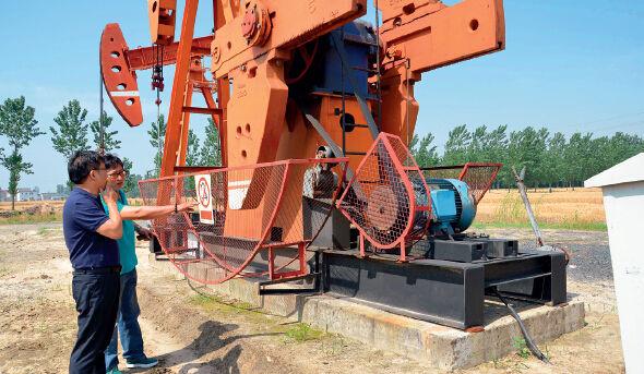 p38江苏油田试采一厂高徐采油管理班班长许志刚向东方吊架公司总工程师吴利群介绍张紧装置使用情况。