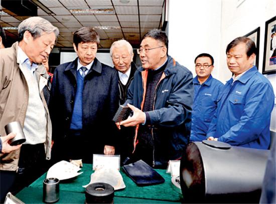 p52-1 初长祥(右三)向行业专家介绍柳工自主研发的减振降噪产品