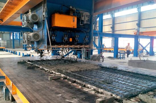 p36 中建七局的生产线上,布料机正向钢骨架浇筑混凝土。