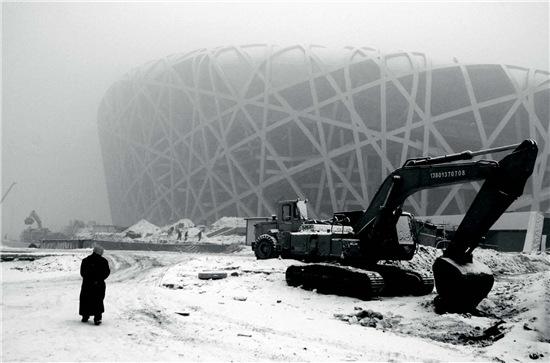 "p48-1 2007 年12 月10 日""鸟巢""工地一片繁忙,工人们迎着大雪继续奋战赶进度。"