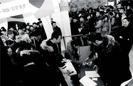 p48-3 2010 年1 月3 日朝阳区东五环某楼盘开盘,火爆的楼市使得300 多名购房者冒着大雪排号选房。