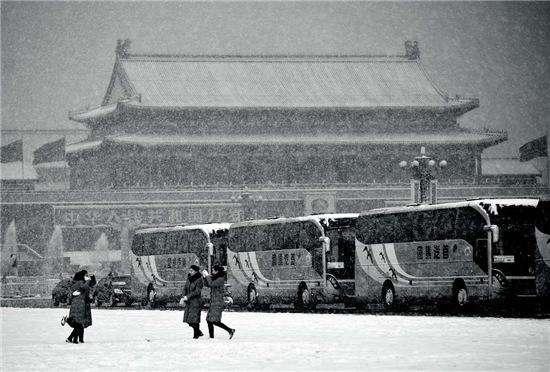 p48-2 2010 年3 月8 日第十一届全国人民代表大会第二次全体会议在人民大会堂召开。会场外,大会服务人员在雪地里留影。