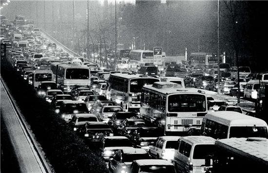 p47-1 2001 年12 月7 日一场中雪致使北京的地面交通大面积瘫痪,高峰时期,整个城区似乎都成了停车场。