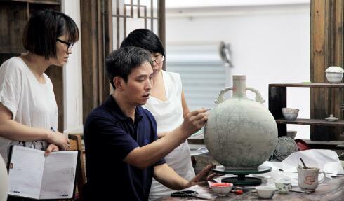 p13 向元华在给画师们仔细讲解手工制作并亲身示范