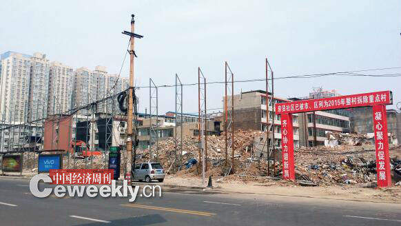 "p47-1 2015 年 5 月 31 日,在社区干部的带头拆迁下,亲贤社区的""城中村改造""拉开帷幕。由于前期""清产核资""及补偿标准等因素,拆迁改造工作推进并不顺利。图为位于体育西路东侧集体所有的商铺率先被拆迁完毕,用于遮挡的围挡正在施工中。(拍摄  2015 年 9 月 16 日)"