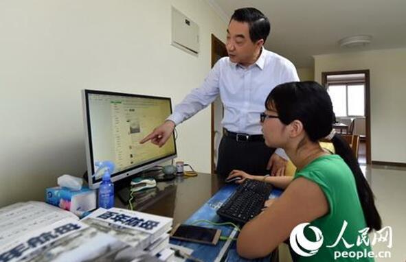 张召忠在电脑屏幕前与编辑商量稿件细节问题。记者翁奇羽 摄
