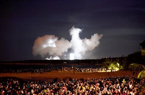 p51-长征七号火箭升空后留下浓厚的白色烟雾,人们用随身携带的手机拍摄。CFP