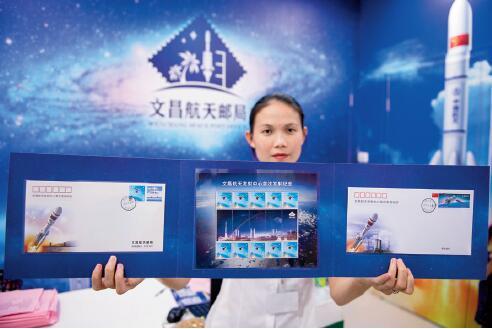 p51-2016 年6 月25 日,海南省文昌市龙楼航天邮局的工作人员展示发售的纪念邮折。CFP