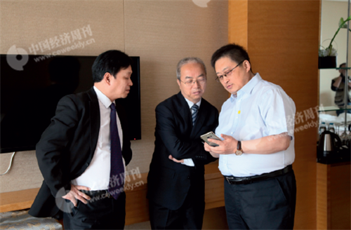 p12(7) 《中国经济周刊》总编助理包锐(右)向榆中农村合作银行董事长周承中(中)展示论坛新媒体报道。
