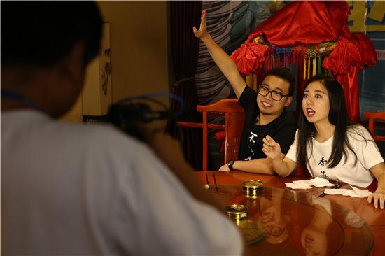 """p48 受邀来北京的""""深圳潮生活""""主编李南青和来自腾讯的男主播正在直播"""" 生吃蝎子"""",累计有超过51万名观众在线收看。"""