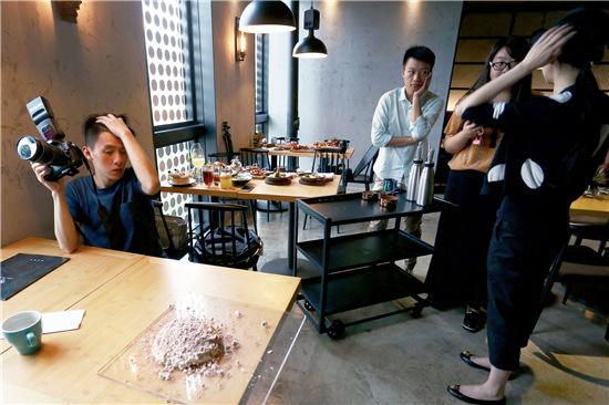 """p50-1 """"北京潮生活""""的工作人员在探店,为这家餐厅客户的推广采集素材。"""