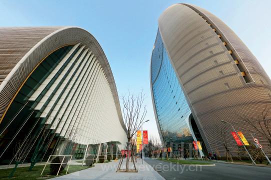 """p132 已经连续举办16 届的中国经济论坛,在新启用的人民日报社报告厅举行。报告厅被大家亲切地称为""""鼠标楼"""",因为整体形状像一个鼠标,与人民日报社新媒体大厦主楼呼应成趣。报告厅大楼的设计呈现出有机而动态的完美流线形状,在蓝天白云下显得优雅而富有科技感。"""
