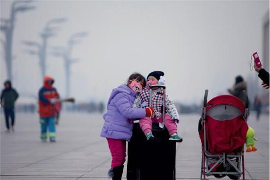p50 2016年12月11日,北京雾霾再度来袭,在鸟巢附近广场上,一位母亲正在给两个孩子合影。