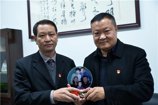 """新安县县委书记王玉峰(左)向党员干部赠送廉洁寄语""""全家福"""""""