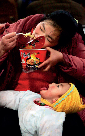 p30 2006 年1 月18 日,西客站候车室,一位母亲为了喂年幼的孩子把方便面咬成一小截,孩子却等不及地张大了嘴巴 。此图为CFP 年度日常新闻类金奖。