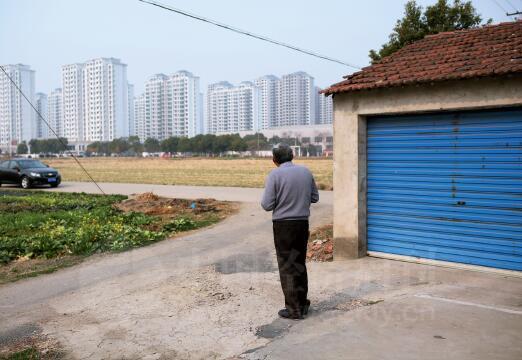 p46-2村里的不少村民在等着拆迁,远处的高楼一步步逼近曾经的田地和村庄。