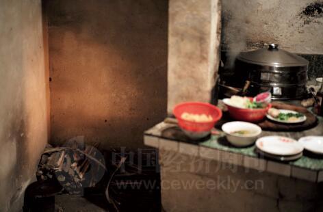 p47-外公依然使用烧柴火的灶台为大家准备年夜饭。而年轻人吃完年夜饭,则赶紧回到有空调、带卫生间、能看网络电视的回迁房里。村子里就剩下老人和麻将声。
