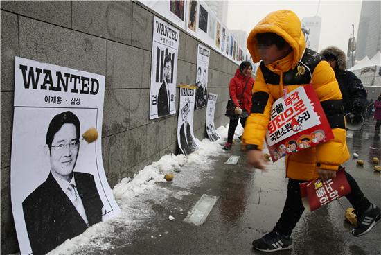 "p49 1月21日, 韩国民众计划进行第13次烛光集会,并在墙上贴上三星电子副会长李在镕等""干政门""涉事人的图片,投球出气要求尽快将其逮捕。"
