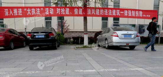p29-2 雄县人民政府附近一栋建筑外悬挂的打击违建的宣传语。