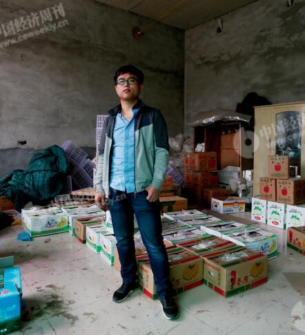 p29-1 程新在自己家中。他的父母在镇上贩卖水果,家中一间暂未装修的房内堆满各种水果。