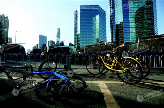 p046北京八王坟东公交车站前,违规停放的共享单车被人推倒。