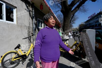 p47-1一位住在南河沿大街附近的居民,协助ofo 线下运维人员将部分有损的单车集中摆放,并制作了提示牌。