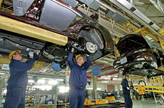 57 浙江吉利汽车有限公司总装二厂工人在车间组装汽车。视觉中国