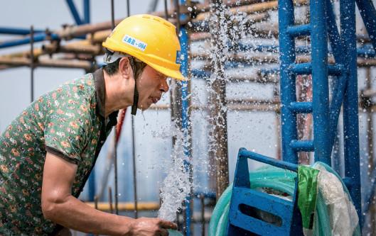 p43(3) 四川德阳,一名工人在高温下用水管冲洗降温。