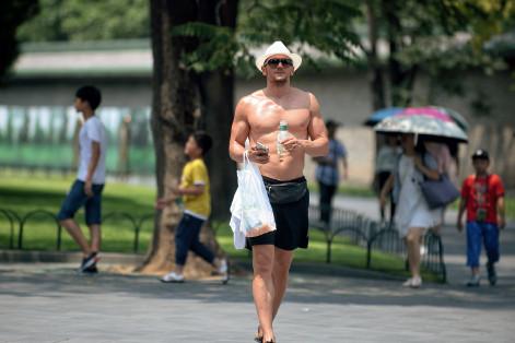 p45(2) 7月12日,一名外国游客脱掉上衣、身穿短裤,但依旧大汗淋漓。