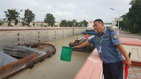 2、邵伯船闸工作人员在船闸现场指挥船舶有序过闸