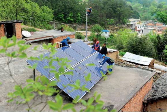 P81  安徽省六安市金寨县金刚台村,电力技术人员对贫困户的光伏发电设备进行并网前检查测试。