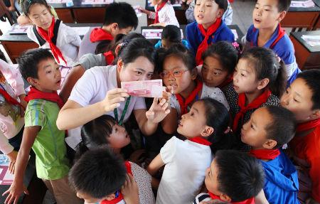 3、江阴农商行工作人员教小学生识别人民币真伪 摄影 杨婧
