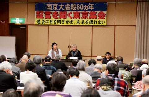 """p29(2)▲ 12 月13 日晚,""""南京大屠杀80 周年证言集会""""在东京全水道会馆举行,来自中国、日本和其他国家的有识之士约200 人参加。图为参会者观看揭露历史真相的各国出版物。"""