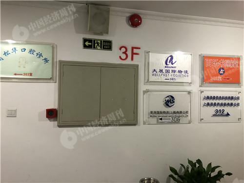 周家嘴路1220弄1号楼3楼楼道内的指示牌已无钱宝网LOGO(宋杰摄影)