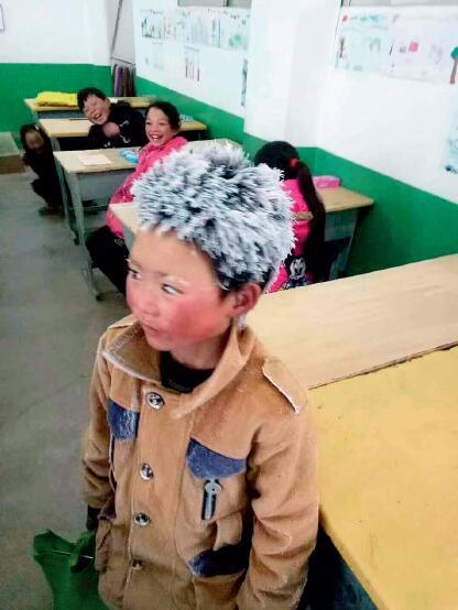 """43 """"冰花男孩""""是云南省鲁甸县新街镇转山包小学的学生。1 月8 日上午,他走了近一个小时的山路,赶到学校参加期末考试,到达教室时头上已经结满冰霜,远看去,像是长了一头白发。"""
