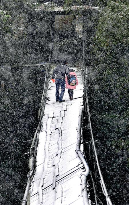 44 2010 年12 月15 日,四川都江堰市紫坪铺镇沙湾村,清洁工赵继红试图走过残缺木板、扭曲倾斜的索桥,送女儿上学。但因下雪打滑,女儿不敢上前,只得返回家中。