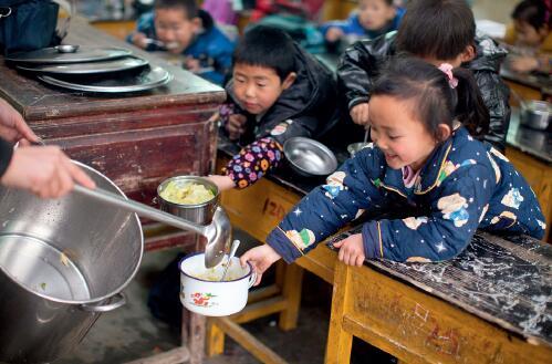 45-2 2013 年2 月28 日,江西鄱阳县鸡峰村小学的老师给学生们发放免费午餐。米饭每人四两(管吃饱);每餐保证孩子一菜一汤,其中有一份是荤菜;煮鸡蛋一周每人一个。这些孩子们从此告别了中午不吃饭或吃腌菜的生活。<p>图片来源: 视觉中国</p>