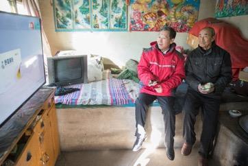 京东集团党委书记龙宝正帮老人调试新装的电视机