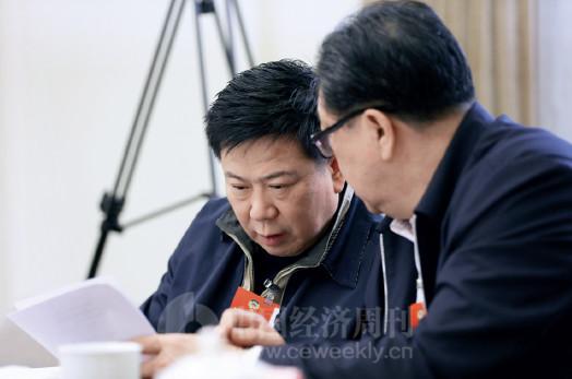 p81 全国政协委员、中国太平保险集团董事长王滨(左)在政协经济界别小组讨论会上讨论提案。