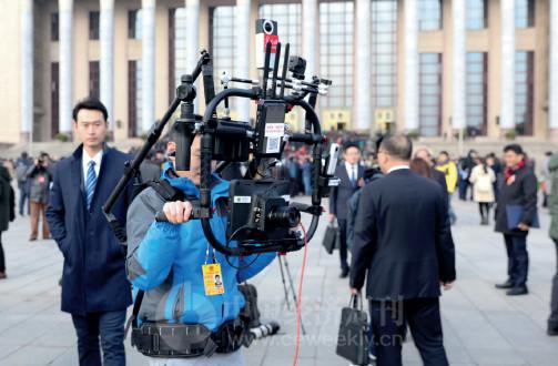 p85 人民大会堂外,一名记者在操作新型设备。