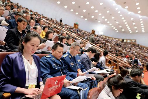 p84(2) 《中国经济周刊》记者张璐晶在十三届全国人大一次会议开幕会上聆听政府工作报告。