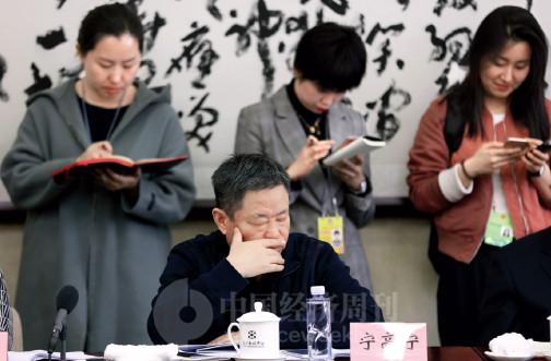 p85 中外媒体记者们在会场内站着记录委员们的发言。