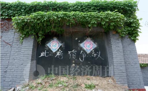 """p30-艺术家马万明在辛店村的住宅,门前被村民堆放土堆,门上写着""""此房有争议""""。《中国经济周刊》记者 胡巍I 摄"""