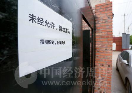 p31-14 月28 日周家强行滞留张海涛家后,张海涛在家门上贴出警示。《中国经济周刊》记者 胡巍I 摄