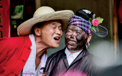 """50-4 8 月29 日,贵州省黔东南苗族同胞在欢度""""吼贝节"""",群众之间用锅烟墨(锅底灰)相互抹脸,嬉戏逗乐,祈愿秋收来临时五谷丰登,来年风调雨顺。"""