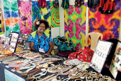 55-2 莫尔兹比港的商贩在等待顾客光临,他们售卖着当地传统纹饰布料、首饰或纪念品。