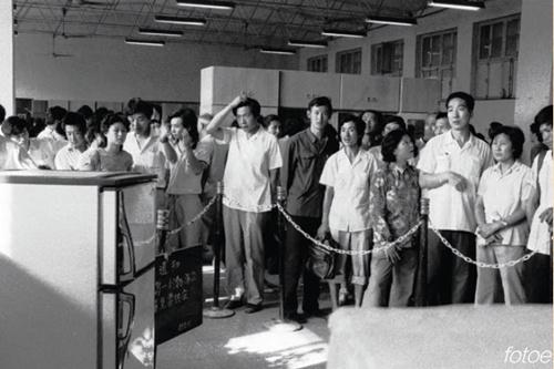 """35-1 1988 年9 月,北京西单商场,人们望着电冰箱旁""""凭票""""的通知,感到很无奈。"""