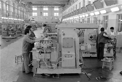 """p39-北京第一机床厂自1987 年1 月开始实行""""两保一挂""""承包经营责任制后,给企业注入了新的活力。这个厂的""""七五""""重点改造项目装配车间总装线,工期原需8个月,实际只用了4 个半月。(新华社)"""