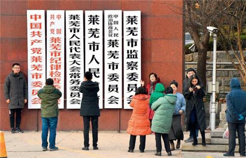 p94-国务院批复同意,撤销莱芜市,将其所辖区域划归济南市管辖。市民纷纷来到党政机关门前合影留念。(视觉中国)
